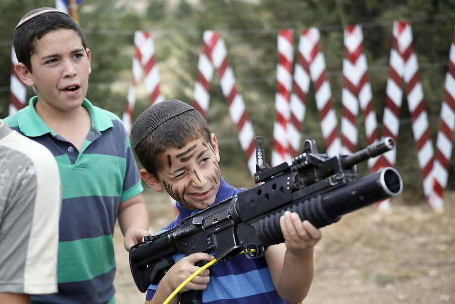 Armed for independence day: In the West Bank settlement of Efrat, an Israeli boy plays with an assault rifle during a 