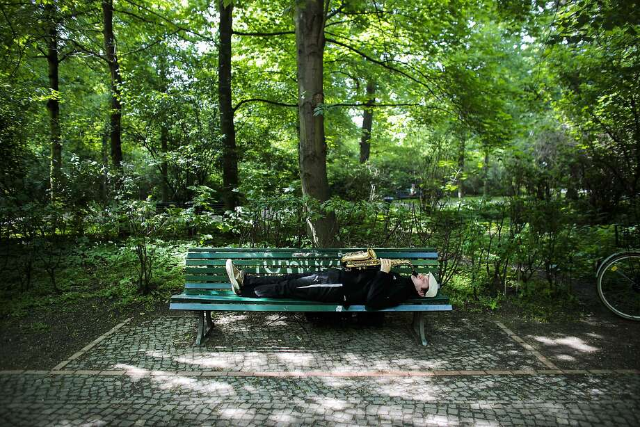 Lying down on the job: Saxophonist and street musician Alex Jam performs horizontally for passers-by at the Tiergarten park near the Brandenburg Gate in Berlin. Photo: Markus Schreiber, Associated Press