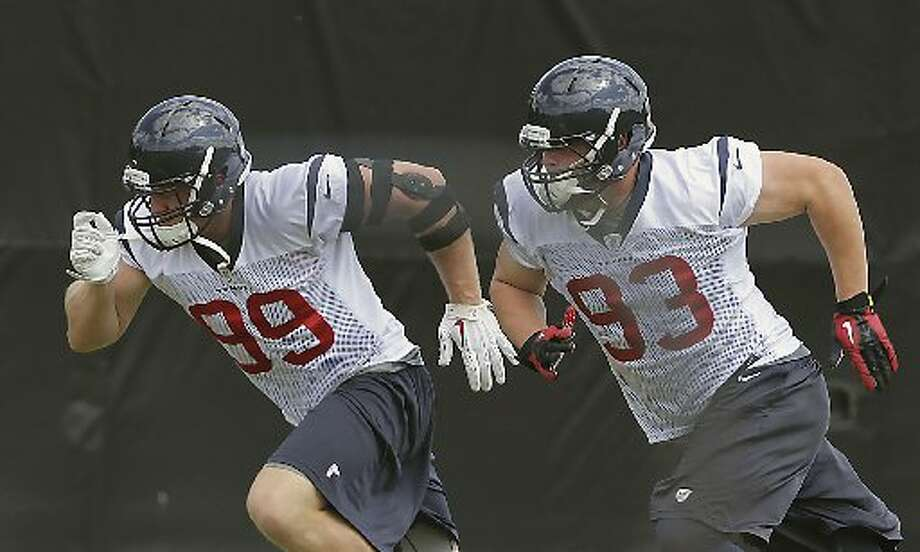 Texans defensive ends J.J. Watt, left, and Jared Crick take part in a drill. Photo: James Nielsen, Houston Chronicle