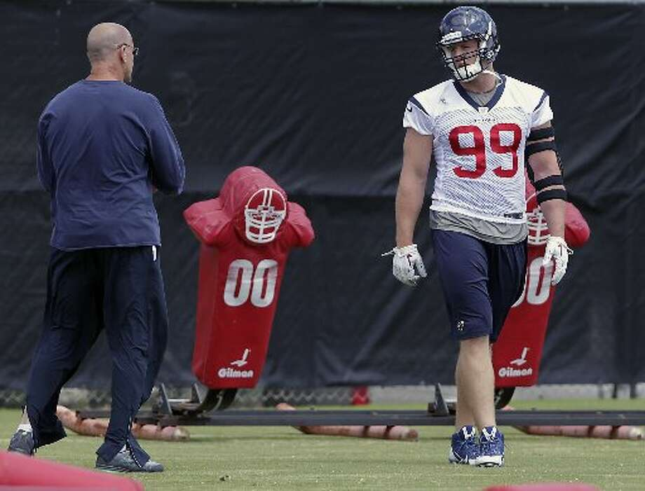 Texans defensive line coach Bill Kollar, left, speaks with defensive end J.J. Watt, right, during a drill. Photo: James Nielsen, Houston Chronicle