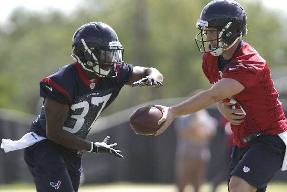 Texans quarterback T.J. Yates, right, hands the ball off to running back Ray Graham. Photo: James Nielsen, Houston Chronicle