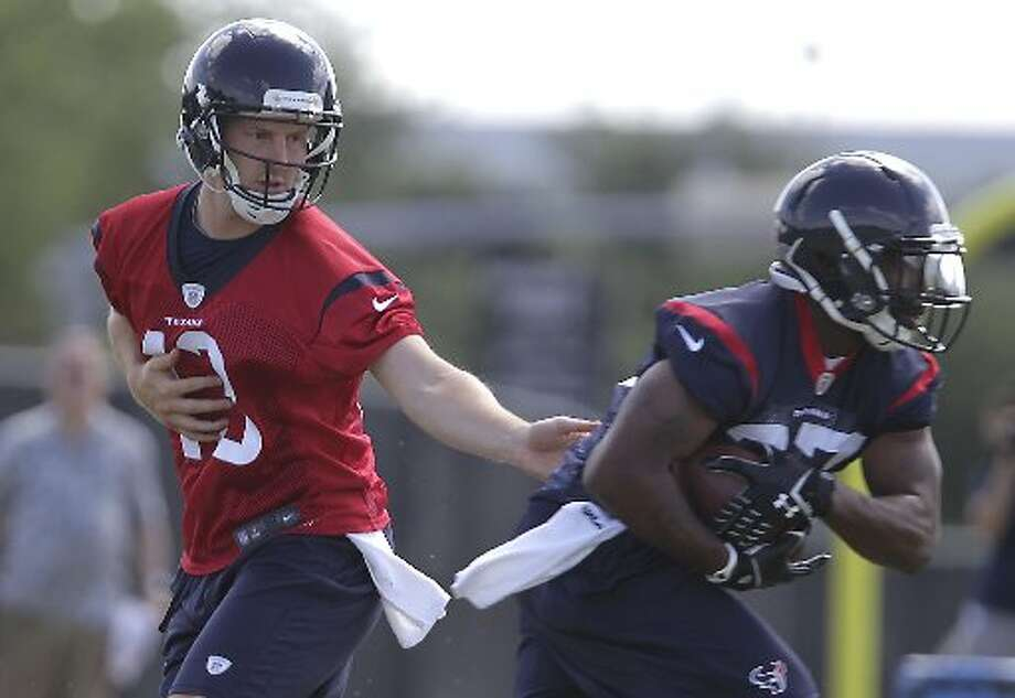 Texans quarterback T.J. Yates, left, hands the ball off to running back Ray Graham. Photo: James Nielsen, Houston Chronicle