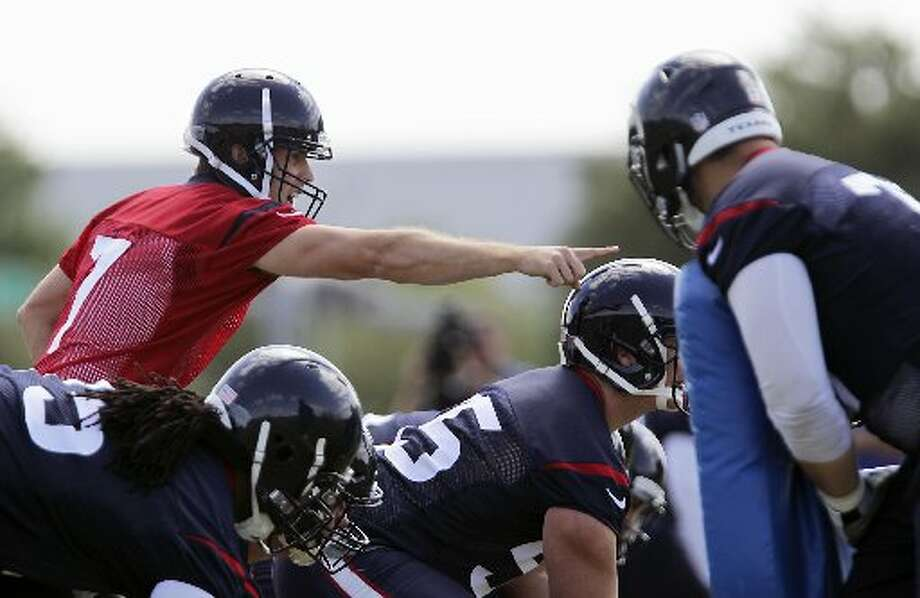 Case Keenum, left, signals during a drill. Photo: James Nielsen, Houston Chronicle