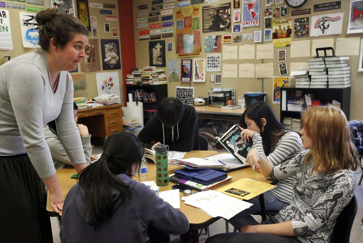Teacher Rachel Sadler, left, listens to a question from Anzhela Klimenko,18, from Kazakhstan, far right, as students (from left of Sadler) Elaine Huang, 18, from China, Haijuan Chen, 19, from China, Tao Wang, 18, from China and Lucy Zhu, 18, from China, read Persepolis during Sadler's 12th grade English class May 6, 2014 at San Francisco International High School in San Francisco, Calif.