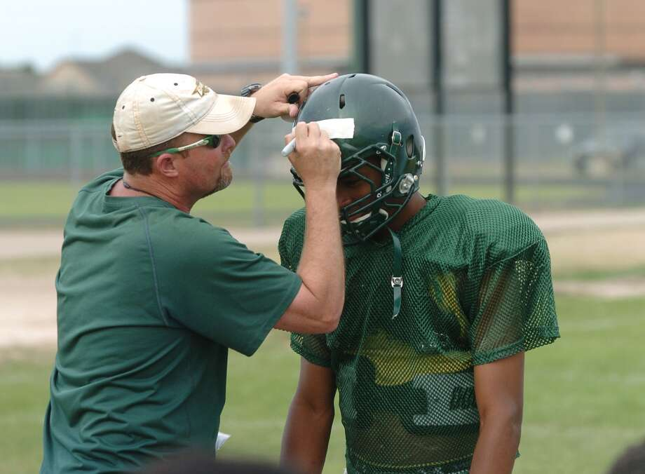 Cy Falls football coach Kirk Eaton, left, awards quarterback Nate Dalton, senior, player of the day, following spring practice last week. Photo: Eddy Matchette, Freelance / Freelance