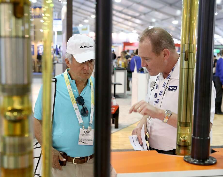 Randy Dewerff (right) with Dover Artificial Lift explains to Earl Herrera with Sonerra Resources Corp. how the Harbison Fischer pubs work on May 6, 2014 in the OTC Pavillion in Houston, TX. (Photo: Thomas B. Shea/For the Chronicle) Photo: Thomas B. Shea, For The Chronicle