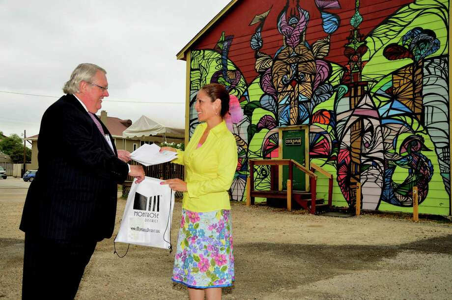 Montrose District's chairman Claude Wynn and ambassador Marie Cortes Matte use promotional materials to publicize the district, which includes restaurants, museums and distinctive buildings such as Cecil's Pub, background. Photo: Jimmy Loyd / freelance