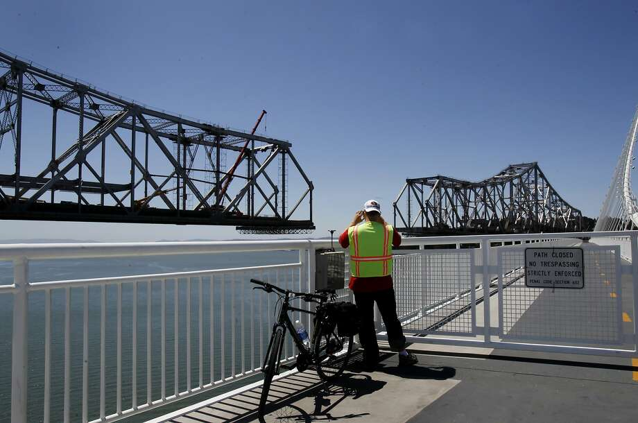 A cyclist photographs the old eastern span from the new, where maintenance worries have been reviewed. Photo: Brant Ward, The Chronicle