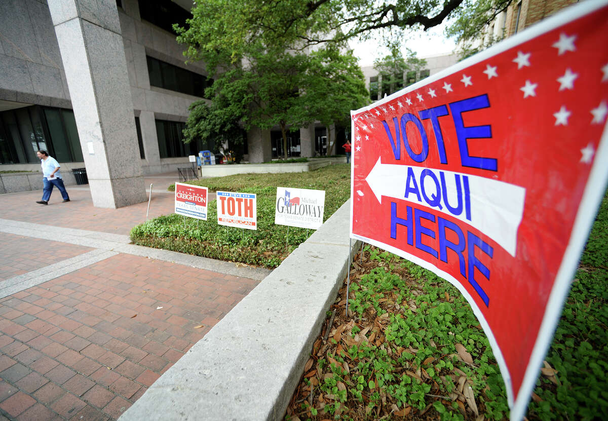 People walk past signs advertising early voting options outside the Jefferson County Courthouse on Thursday afternoon. Early voting for the May 10th special election began Thursday at the Jefferson County Courthouse. The voters will decide on a new state senator to represent District 4 to replace Tommy Williams, who resigned in 2013. Photo taken Thursday, 5/1/14 Jake Daniels/@JakeD_in_SETX