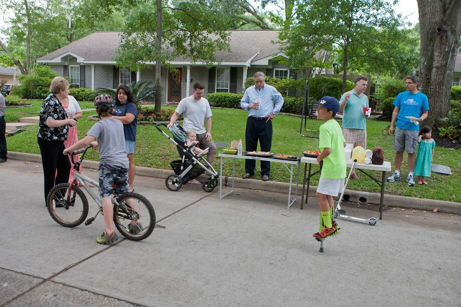 Bobby Herrera, 10, gets exercise on his pogo stick while Afton Village neighbors chat.  Get-togethers including progressive dinners are common in the community. Mingling are: Gay Donehoo, left, Judy Herrera, Ryan Woods, 10; Denise Woods,  James Storey, Nathaniel Storey, 1; Mike Fuqua, Paul Schneidau, Paul Morin and Natalie Morin, 3. Photo: R. Clayton McKee, Freelance / © R. Clayton McKee