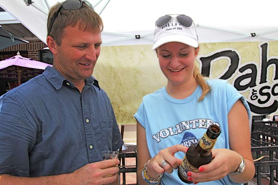 Rob Tichenor of Katy and Nathalie Crass, Rotaract District Governor, read the contents of a Rahr & Sons beer bottle at the 2012 festival.Rob Tichenor of Katy and Nathalie Crass, Rotaract District Governor, read the contents of a Rahr & Sons beer bottle at the 2012 festival. Photo: Suzanne Rehak, Freelance Photographer