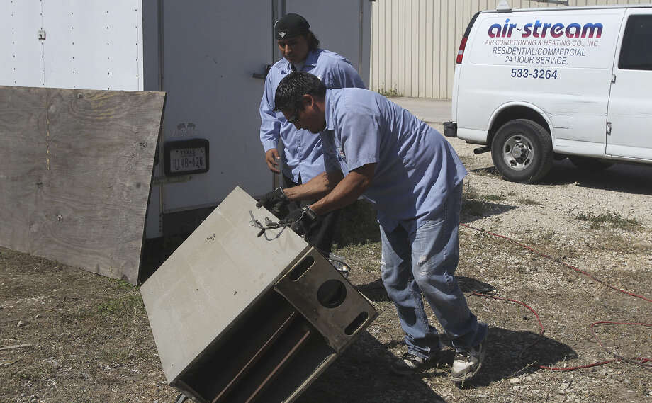 Air-Stream Air Conditioning & Heating Co. Inc. employees Genaro Ortiz (foreground) and Juan Barajas move equipment at the firm's location on Dividend Drive. The company has been in business for 40 years. Photo: John Davenport / San Antonio Express-News / ©San Antonio Express-News/John Davenport