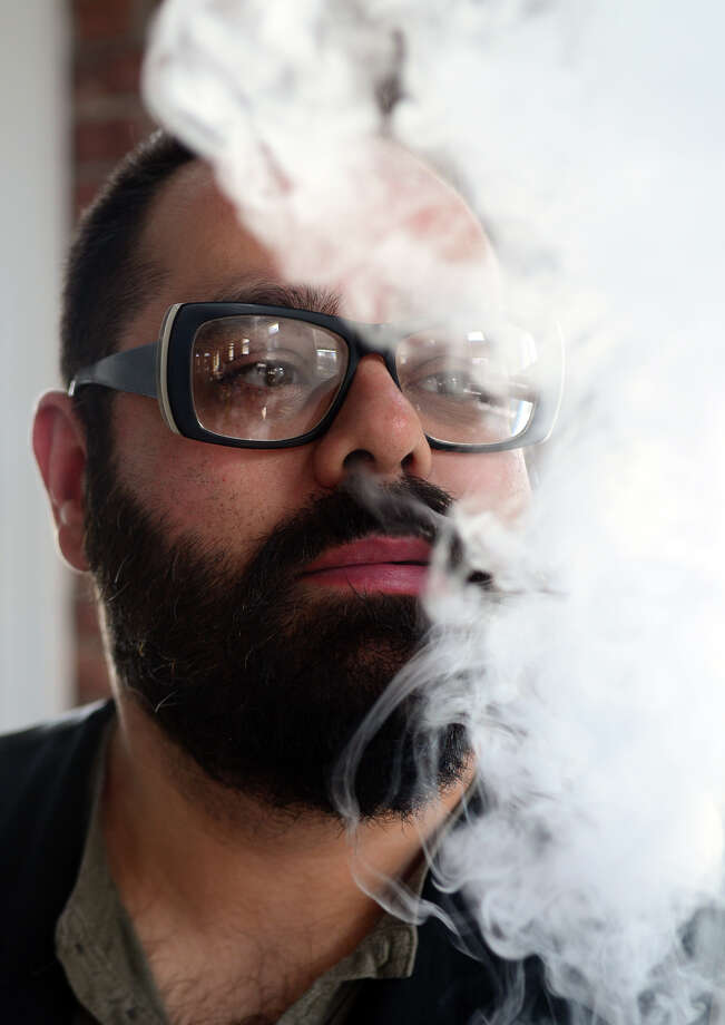 Marcos Garcia, Co-owner of Sovereign Vapors in Fairfield, Conn., exhales while using an e-cigarette at the new vapor lounge on Tuesday May 6, 2014. Photo: Christian Abraham / Connecticut Post