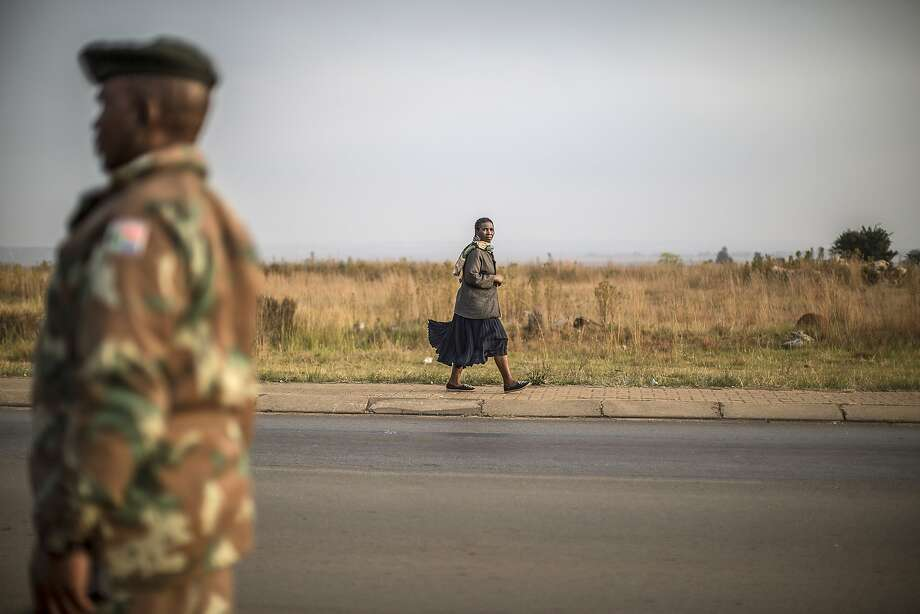 TOPSHOTS A South African woman passes in front of a soldier stationed to patrol the restive Bekkersdal township on May 6, 2014. South Africa goes to polls on May 7, 2014 in the fifth democratic elections after the fall of apartheid in 1994. AFP PHOTO / MARCO LONGARIMARCO LONGARI/AFP/Getty Images Photo: Marco Longari, AFP/Getty Images