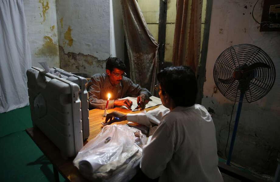 Election officials set up a polling booth by candlelight at a school on the eve of polling in Allahabad, in the northern Indian state of Uttar Pradesh, Tuesday, May 6, 2014. The multiphase voting across the country runs until May 12, with results for the 543-seat lower house of parliament expected on May 16. (AP Photo/Rajesh Kumar Singh) Photo: Rajesh Kumar Singh, Associated Press