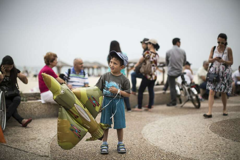 TEL AVIV, ISRAEL - MAY 6: A young boy plays with a plane-shaped balloon on the beach in the Mediterranean sea as people wait for the  military air show marking the 66th anniversary of Israel's independence to start on May 6, 2014 in Tel Aviv, Israel. The day marks when David Ben-Gurion, the Executive Head of the World Zionist Organization declared the establishment of a Jewish state in Eretz- Israel. (Photo by Ilia Yefimovich/Getty Images) *** BESTPIX *** Photo: Ilia Yefimovich, Getty Images