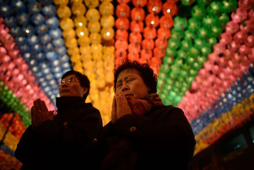 TOPSHOTS Worshippers pray beneath lanterns during a ceremony marking Buddha's birthday at the Jogyesa temple in Seoul on May 6, 2014. Buddha's birthday in South Korea is celebrated with a week-long festival usually ending on the same day as Vesak Puja in other parts of Asia. AFP PHOTO / Ed JonesED JONES/AFP/Getty Images