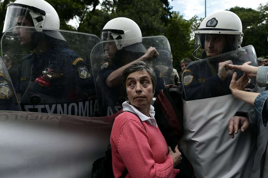 TOPSHOTS Civil servants face riot forces as they demonstrate against austerity measures imposed under the debt-mired country's international bailout commitments in central Athens on May 6, 2014. AFP PHOTO / ARIS MESSINISARIS MESSINIS/AFP/Getty Images Photo: Aris Messinis, AFP/Getty Images