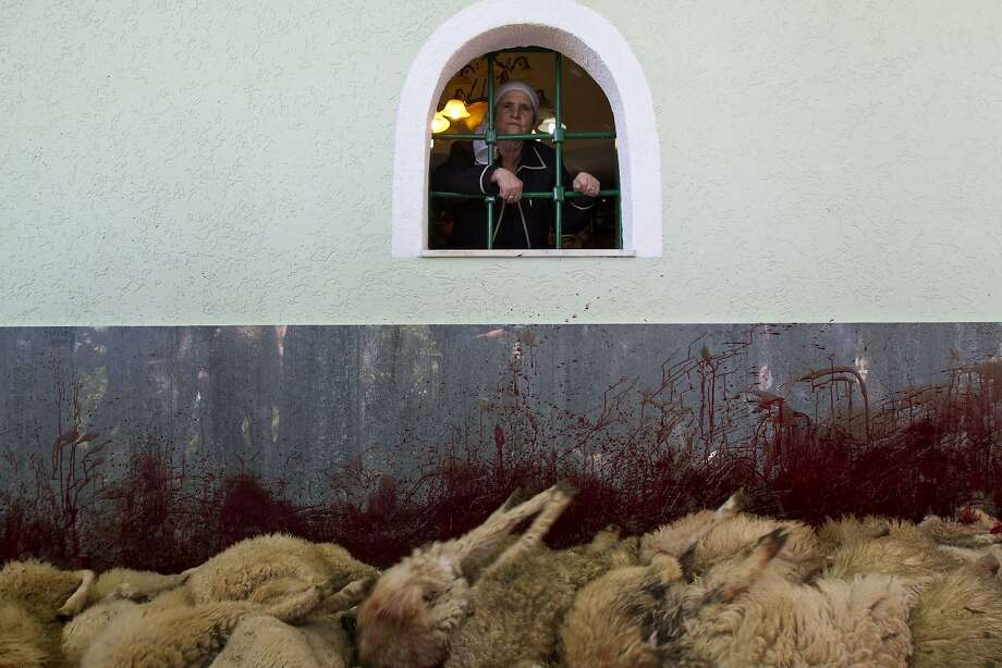 A woman looks out of a window where sheep are slaughtered during celebrations of the traditional feast of Saint George's Day, which is observed by several nations, kingdoms, countries, and cities of which Saint George is the patron saint, in the village of Babaj i Bokes, western Kosovo, Tuesday, May 6, 2014. (AP Photo/Visar Kryeziu) Photo: Visar Kryeziu, Associated Press