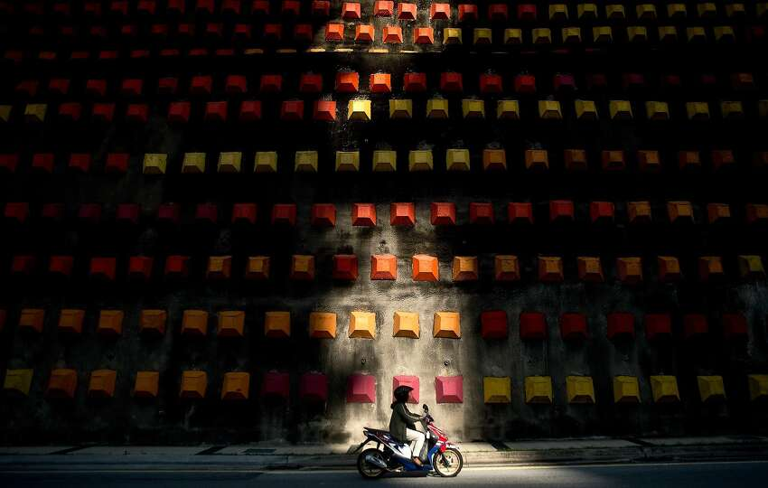 TOPSHOTS A motorist rides to work past a decorated wall in Kuala Lumpur on May 6, 2014. According to a Michingan University report earlier this year, Malaysia is ranked among the top 20 most dangerous countries for road users. AFP PHOTO/ MANAN VATSYAYANAMANAN VATSYAYANA/AFP/Getty Images