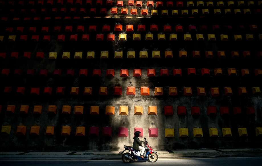 Way to go, Malaysia!A motorcyclist rides to work past a decorated wall in Kuala Lumpur.   According to a Michigan University report earlier this year, Malaysia is ranked among the   top-20 most dangerous countries for motorists. Photo: Manan Vatsyayana, AFP/Getty Images
