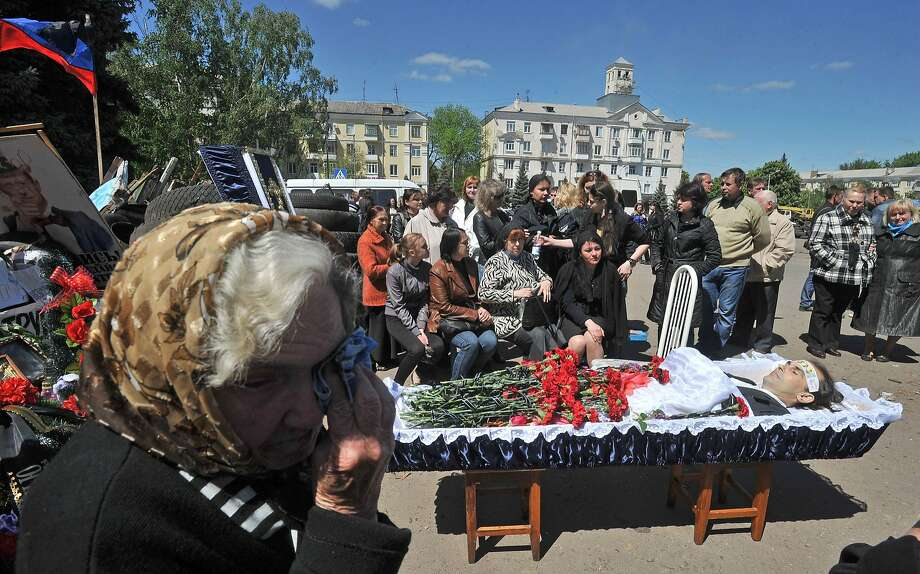 TOPSHOTS People mourn during the funeral ceremony for a pro-Russian activist killed during combat with Ukrainian troops in Kramatorsk, eastern Ukraine, on May 6, 2014. The death toll from a military offensive in a flashpoint town in east Ukraine rose to at least 34, officials said on May 6, amid fresh warnings of civil war and the shutdown of a major airport in the region.     AFP PHOTO/ GENYA SAVILOVGENYA SAVILOV/AFP/Getty Images Photo: Genya Savilov, AFP/Getty Images