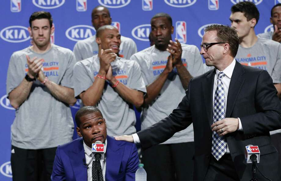 Thunder coach Scott Brooks (right) puts a hand on Kevin Durant's shoulder as the Texas-ex's teammates applaud Tuesday in recognition of his MVP season. Photo: Sue Ogrocki / Associated Press / AP