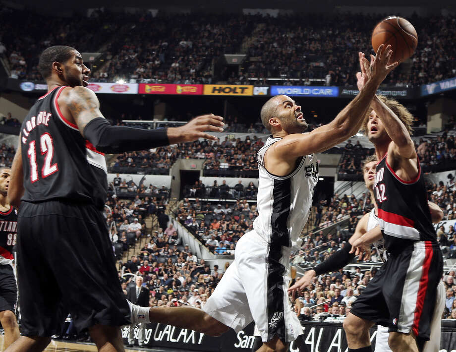 Tony Parker scoops a layup between Portland forward LaMarcus Aldridge (left) and center Robin Lopez in the second half of the Spurs' Game 1 victory Tuesday. Photo: Photos By Edward A. Ornelas / San Antonio Express-News / © 2014 San Antonio Express-News