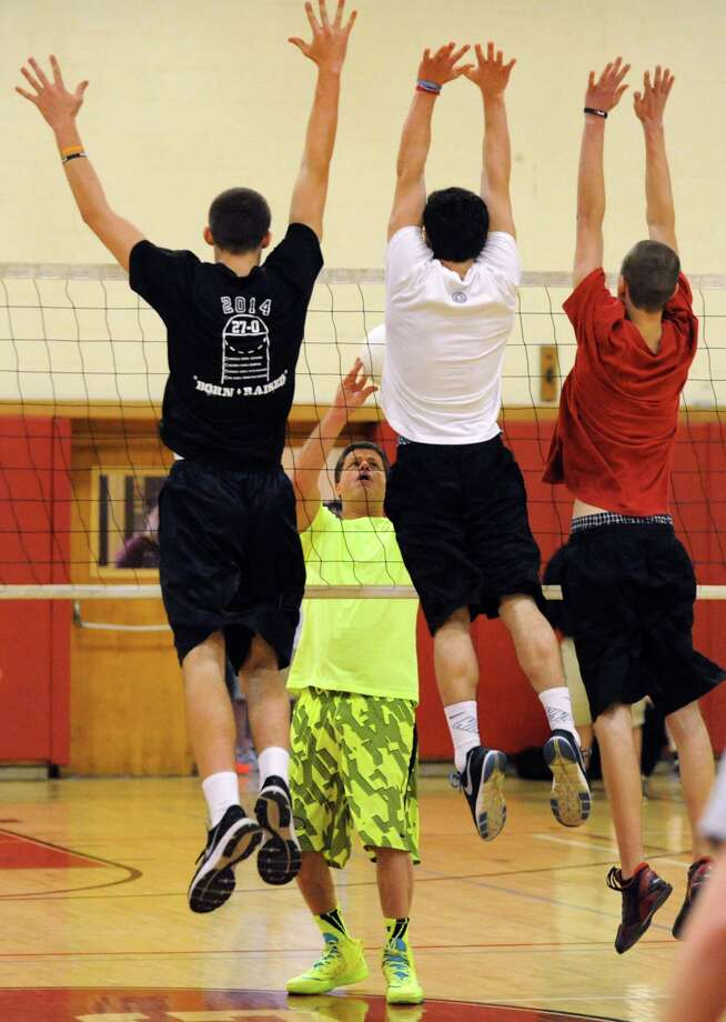 Bob Holmes of Plymouth, N.H., center, who's a one-man volleyball team, takes on a mixed physical education class in a game of volleyball on Tuesday, May 6, 2014, at Scotia-Glenville High in Scotia, N.Y. Defending, from left, are Joe Cremo, Zach Musto and Kyle Bekkering. (Cindy Schultz / Times Union) Photo: Cindy Schultz / 00026781A