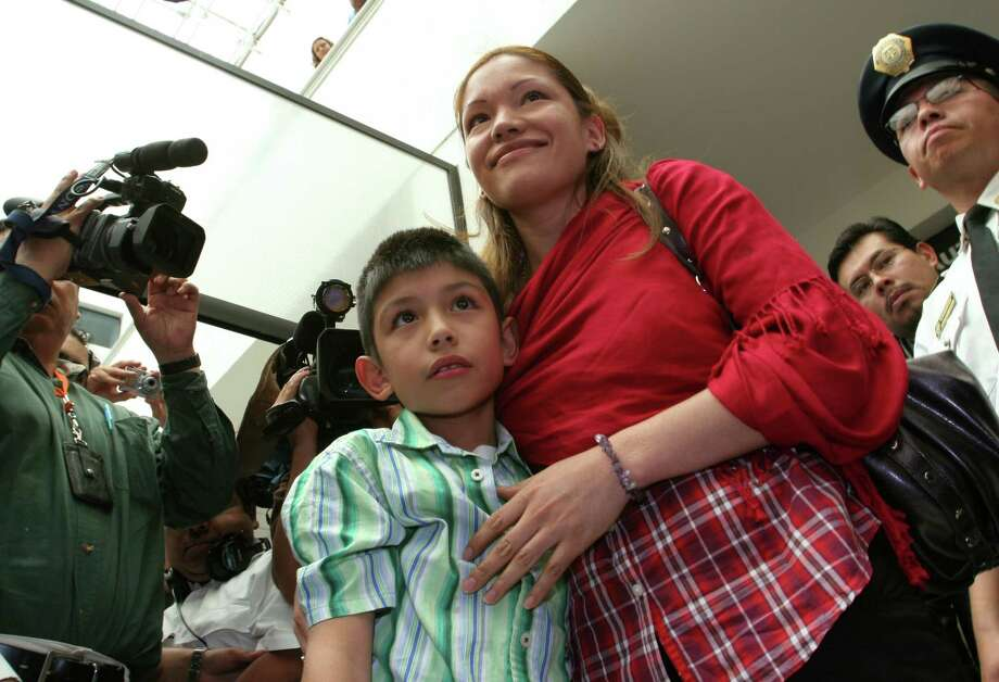 Immigration activist Elvira Arellano stands with her US-born son Saul, 8, upon his arrival to Mexico at the International Airport in Mexico City, Friday, Aug. 31, 2007. Arellano, 32, is a recently deported immigrant who spent a year living inside a Chicago church to avoid deportation and separation from her son. Saul is in Mexico to try to renew his US passport. Photo: Marco Ugarte, AP / AP