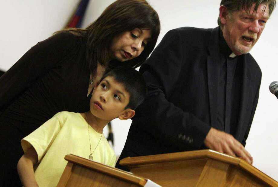 Saulito Arellano, 8, an U.S. citizen, joins his guardians Emma Lozano and the Rev. Walter Coleman, right, at a rally at Iglesia Nueva Luz in Cleveland, Monday, Sept. 10, 2007. Arellano's mother Elvira Arellano was deported to Mexico leaving him behind. Photo: Chris Stephens, AP / THE PLAIN DEALER