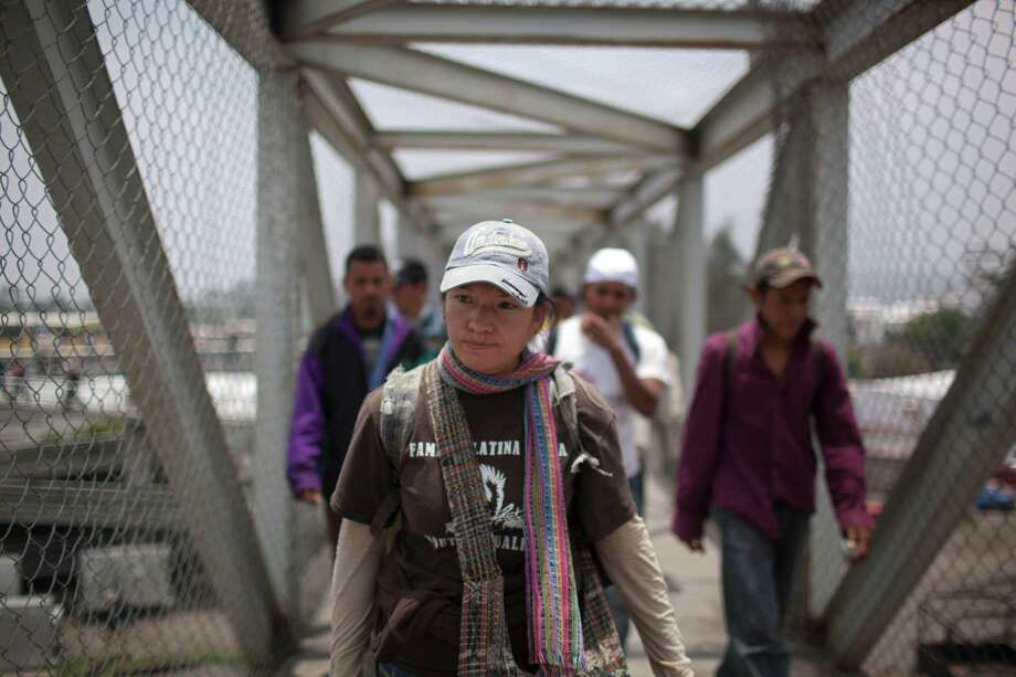 In this May 17, 2012 photo, immigrant rights activist Elvira Arellano walks with Central American migrants toward the city mayor's home to protest violence against migrants, in Lecheria, on the outskirts of Mexico City. While the number of Mexicans heading to the U.S. has dropped dramatically, a surge of Central American migrants is making the 1,000-mile northbound journey this year, fueled in large part by the rising violence brought by the spread of Mexican drug cartels.  Photo: Alexandre Meneghini, Associated Press / AP