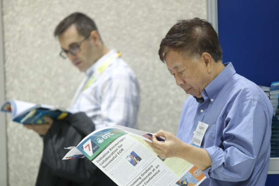 OTC attendee revises the convention's program before the exhibition floor opens, Wednesday, May 7, 2014. (Marie D. De Jesus / Houston Chronicle)