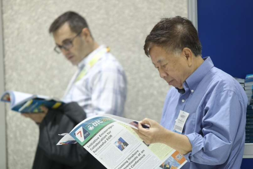 OTC attendee revises the convention's program before the exhibition floor opens, Wednesday, May 7, 2