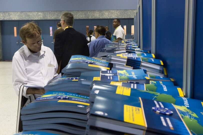 2014 Offshore Technology Conference attendees get their exhibition programs as they wait to enter th