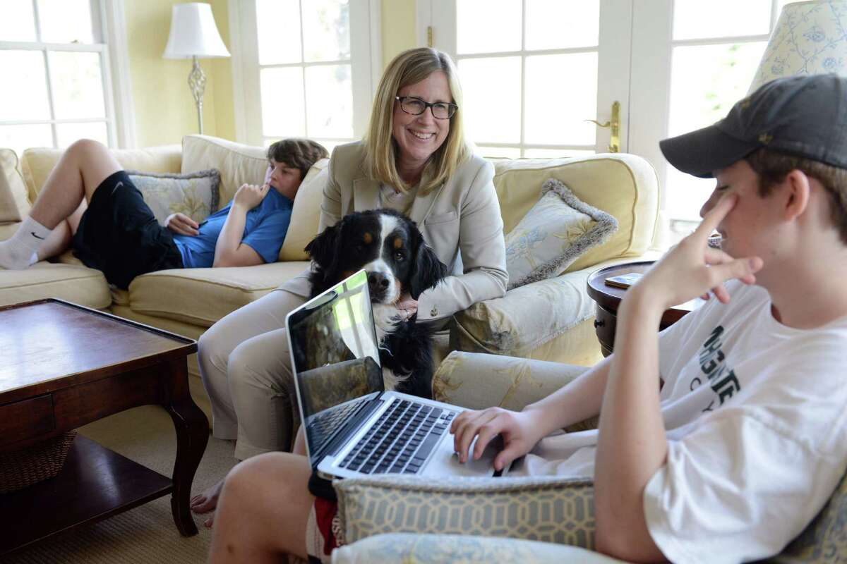 Allison Donaldson sits down with her sons, Jake, left, and Matthew, after work Tuesday, May 6, 2014, at their home in New Canaan.