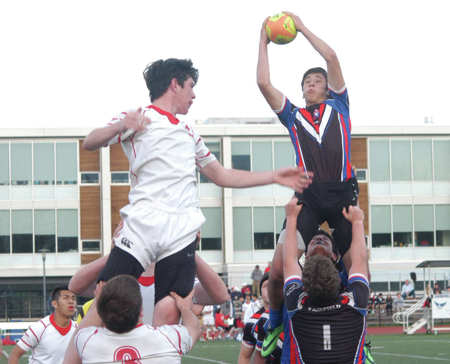 Fairfield co-op rugby player Konstantine Suvorov, right, catches the ball during a line-out while he and Fairfileld Prep opponent Conor Carey are held aloft by teammates in a battle for possession during the Fairfield co-op's 36-17 win at Fairfield Ludlowe's Taft Field on Saturday, May 3. Photo: Andy Hutchison / Fairfield Citizen