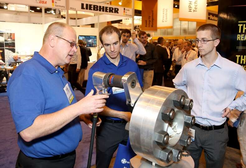 An employee of Hytorc shows a customer the Hytorc bolting system on day three of OTC on May 7, 2014