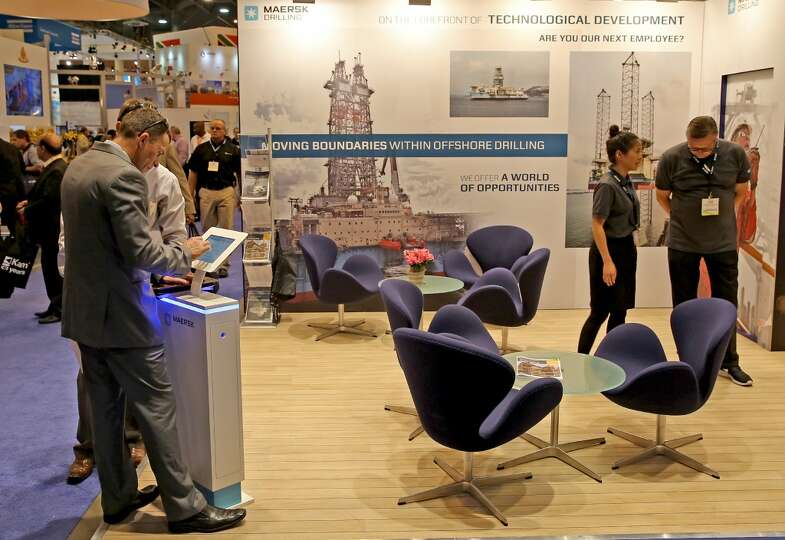 People attend the Maersh Drilling booth on day three of OTC on May 7, 2014 inside the NRG Center in