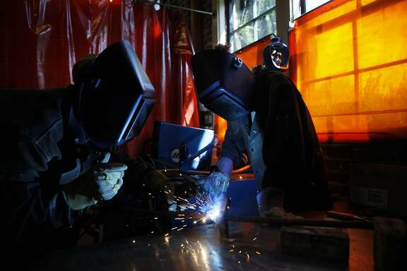 Stanford University students Jeremy Bregman (l to r) and Andrea Stein work in the welding room on their whale sculpture on Friday, May 2, 2014 in Stanford, Calif.