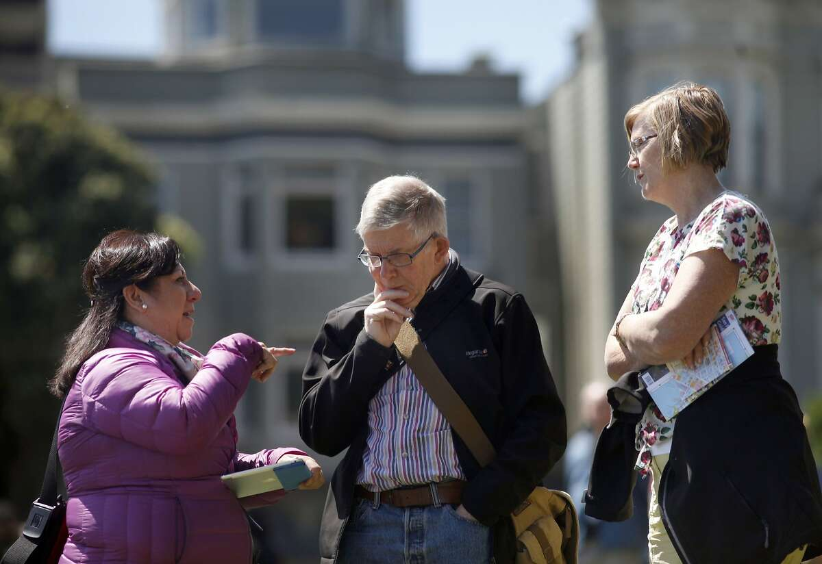 Nancy Rios a tour guide with City Guides tells the story of Alamo Square Park to tourist Roland and Sue Spencer of Dublin, Ireland, Wednesday May 7, 2014, in San Francisco, Calif.