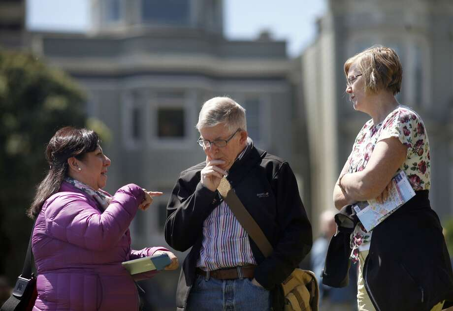 Guide Nancy Rios leads a walking tour, which is allowed in Alamo Square Park, with Roland and Sue Spencer of Ireland. Photo: Lacy Atkins, SFC