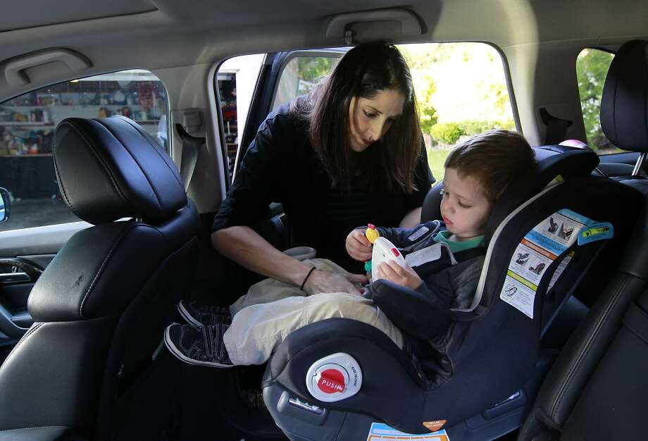 Ashley Burke straps 2-year-old Ryan into a car seat, above, and holds his hand, below, before leaving home. After a prenatal genetic test showed that she was at risk for blood clots, she took blood thinners during her pregnancy. Photo: Paul Chinn, The Chronicle