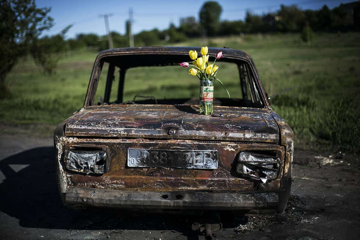 A bouquet of flowers is placed atop the burnt out shell of a car at a location where clashes between pro Russia gunmen and the Ukrainian army took place, 2.5 miles north of Slovyansk, Ukraine, Wednesday, May 7, 2014.