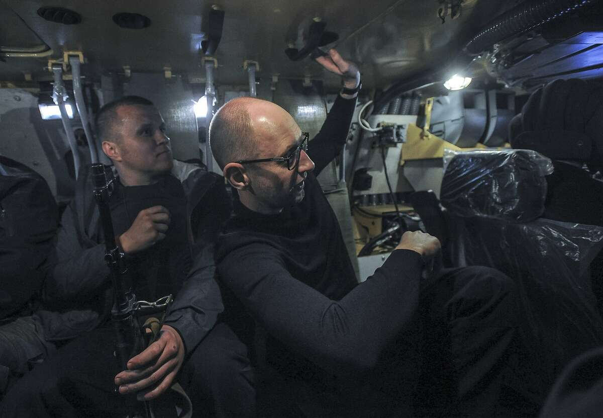 Ukrainian Prime Minister Arseniy Yatsenyuk, right, inspects a Ukrainian army APC on the road at Slovyansk, Ukraine, Wednesday, May 7, 2014. Russian President Putin on Wednesday announced that Russia has pulled back its troops from the Ukrainian border, and called on Ukraine's military to halt operations against pro-Russia activists who have seized government buildings and police stations in cities in eastern Ukraine.(AP Photo/Andrew Kravchenko)