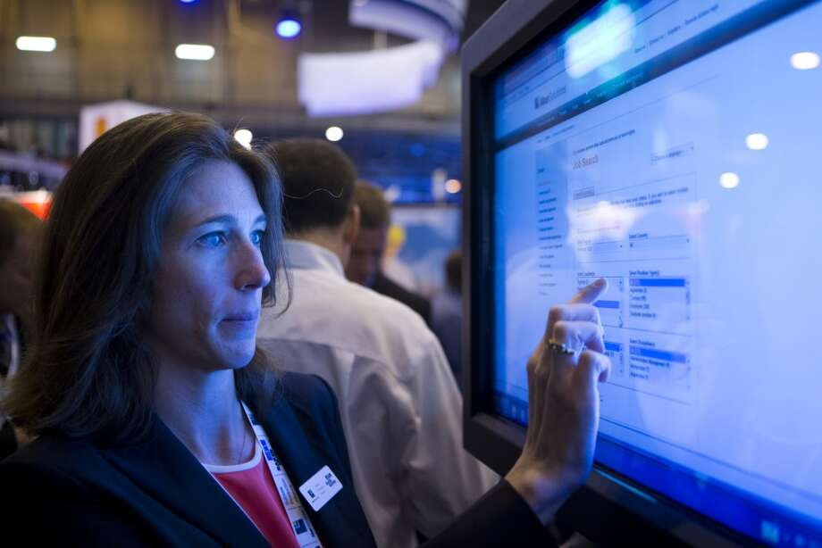 Aker Solutions' Kate Winterton shows the touchscreen facility the company provides for job candidates at their 2014 OTC booth, Wednesday, May 7, 2014, in Houston. ( Marie D. De Jesus / Houston Chronicle ) Photo: Marie D. De Jesus, Houston Chronicle