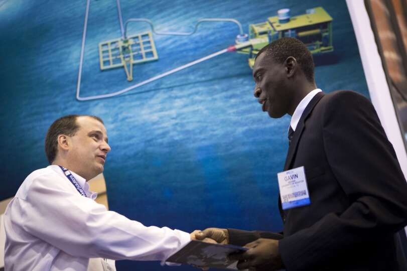 Jeff Lange, left, recruiter for Aker Solutions shakes hands with Gavin Akunna, right, a student at t