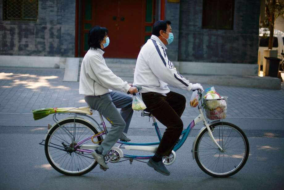 Hey, your back tire leeks: A masked couple ride a tandem bicycle after picking up 