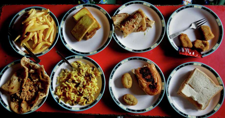 "PHOTOS: School lunches around the wordPAKISTAN: Assorted lunch plates are arranged at a table for students at the Bahria Foundation school in Rawalpindi, Pakistan, Tuesday, May 6, 2014. Most of the kids seen there have home cooked food for lunch. Principal Syeda Arifa Mohsin says the school tries to dissuade parents from fixing junk food for their children. ""If we discover that a child has junk food, we ask his or her parents to please make a little effort for their child's health,"" Mohsin says. Photo: Anjum Naveed, AP / AP"