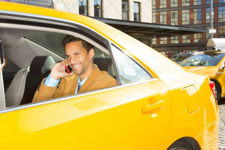 Mixed race businessman on cell phone in taxi 